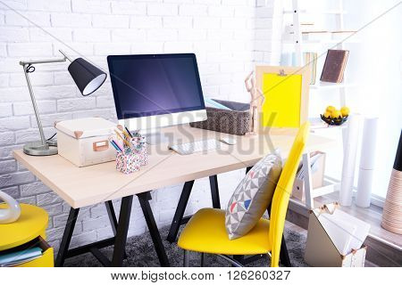 Modern room design. Stylish workplace by the wall.