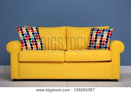 Yellow sofa and multicoloured pillows on a blue wall background
