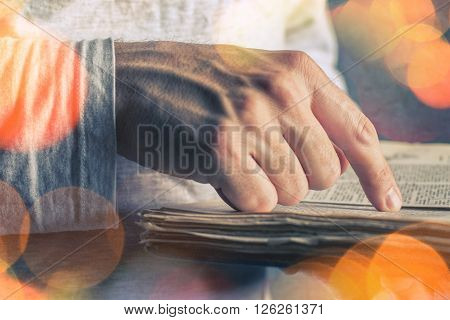 Close up of adult male hands holding vintage book man reading bokeh light effect