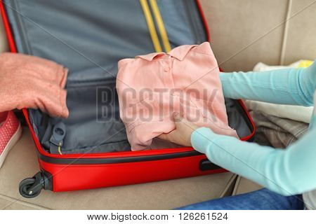 Woman packing her red suitcase, close up
