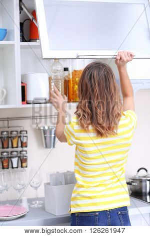 Young woman taking clean dishware in kitchen