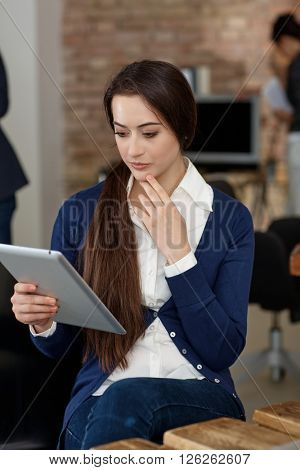 Young businesswoman using tablet computer, thinking.