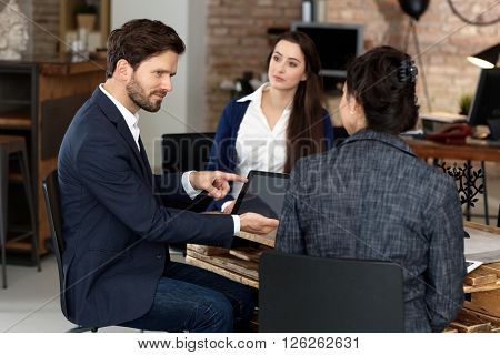 Businesspeople working in office, talking, using tablet computer.