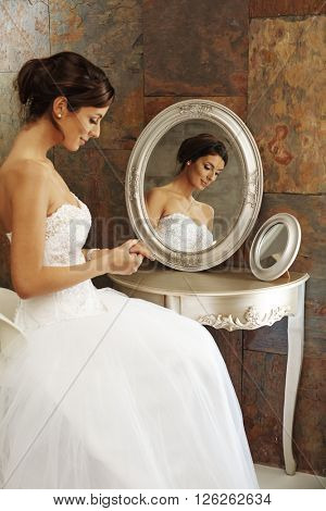 Beautiful young bride sitting on chair front of mirror. Side view.