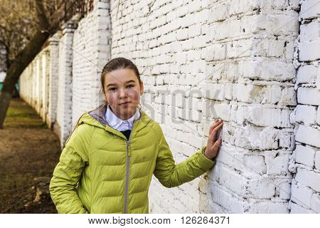 Sad brunette teen girl near a brick wall. Real people, street photography