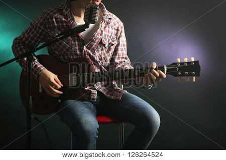 Young man playing electric guitar with microphone on lighted dark background
