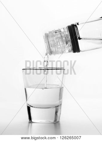 Vodka being poured to a glass. White background. Alcohol concept