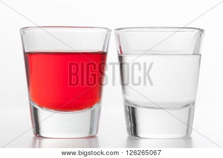 Two glasses of alcohol. One red flavoured, the other clean vodka. White background.