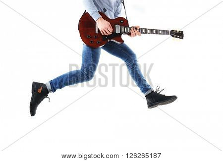 Crazy young man in blue jeans playing electric guitar, isolated on white