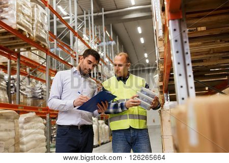 wholesale, logistic, people and export concept - manual worker and businessmen with clipboard and boxes at warehouse