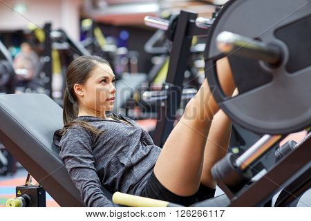 fitness, sport, bodybuilding, exercising and people concept - young woman flexing muscles on leg press machine in gym