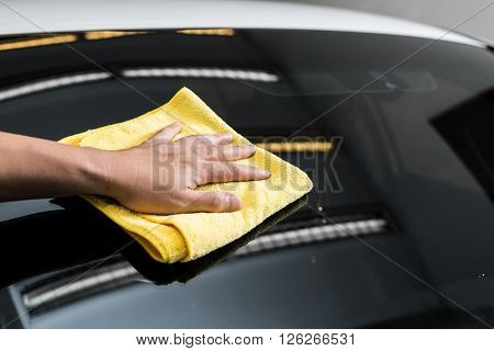 Car detailing series : Hand of worker using yellow towel wiping windshield