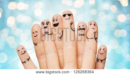 gesture, family, people and body parts concept - close up of two hands showing fingers with smiley faces over blue holidays lights background