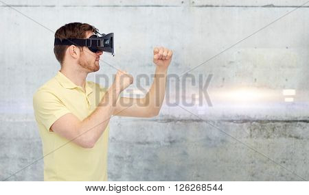 3d technology, virtual reality, entertainment and people concept - young man with virtual reality headset or 3d glasses playing game and fighting over gray concrete wall background