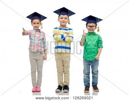 childhood, school, education, knowledge and people concept - happy children in bachelor hats or mortarboards and eyeglasses