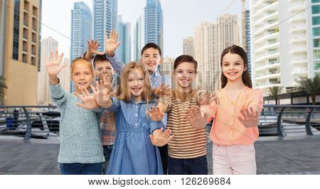 childhood, travel, tourism, gesture and people concept - group of happy children waving hands over dubai city street background