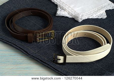 Two strap and two handkerchiefs on denim on a blue wooden background.