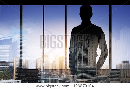 business and people concept - silhouette of business man over double exposure office and city background