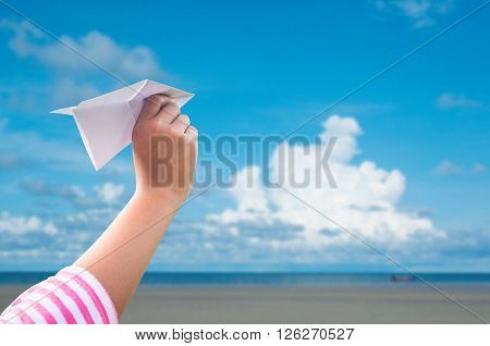 plane paper in children hand over seaand blue sky in cloudy day