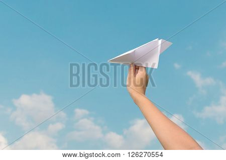 plane paper in children hand and blue sky in cloudy day