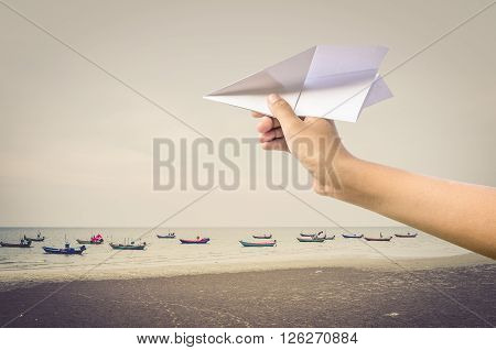 plane paper in children hand over sea and boats vintage style