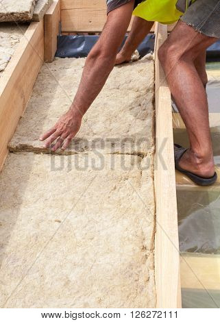 Roofer builder worker installing roof insulation material on new house under construction