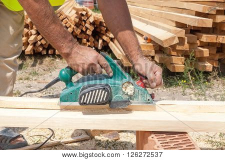 Carpenter working with electric planer close up