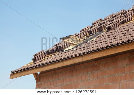 New roof with open skylight natural red tile against blue sky