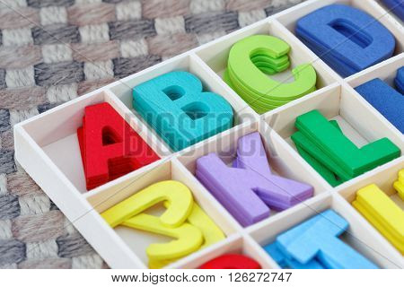 Colourful wooden alphabet block on textured background
