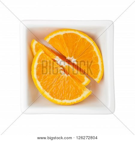Slices of orange in a square bowl isolated on white background