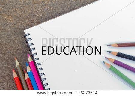 Blank notepad and colorful pencils on the wooden table. View from above. With word EDUCATION.