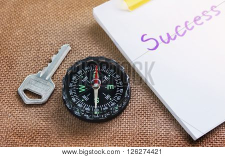 compass with key and blurred text success on paper note business concept