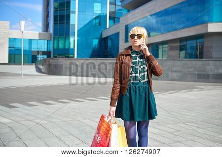 Shopping beautiful woman with bags making phone call on the street