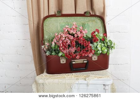 Unusual wedding floral decor composition - flowers in vintage brown suitcase. Old suitcase with flowers. Decoration with flowers. Vintage, rustic, country decor. Floristic decoration. Flowerbed.
