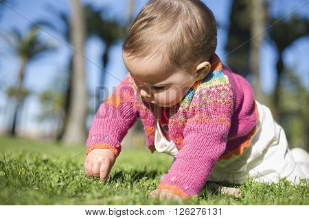 Cute baby girl learning to crawl over the grass park on springtime