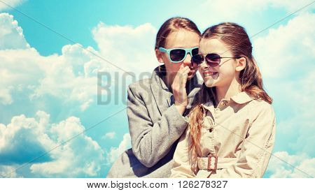 people, children and friendship concept - happy little girl in sunglasses whispering her secret to friends ear or gossiping over blue sky and clouds background