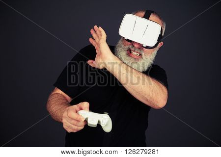 Senior man protect his face playing on the joystick using virtual reality glasses, on black background