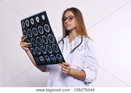Portrait of young woman doctor with stethoscope and MRI scans. Isolated white background