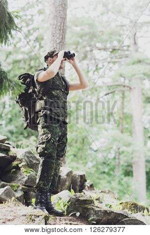 hunting, war, army and people concept - young soldier or ranger with binocular and backpack observing forest