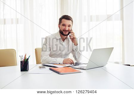 Beard smiling man sitting at the white table working on the laptop and talking on the phone in the modern white office