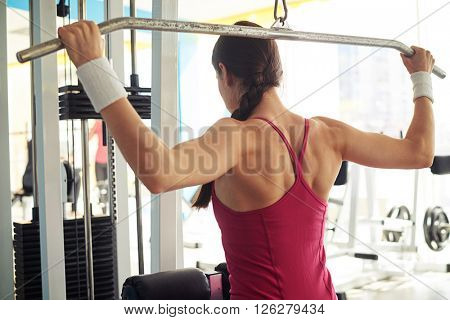 Young Caucasian woman is working out pull-down machine in gym