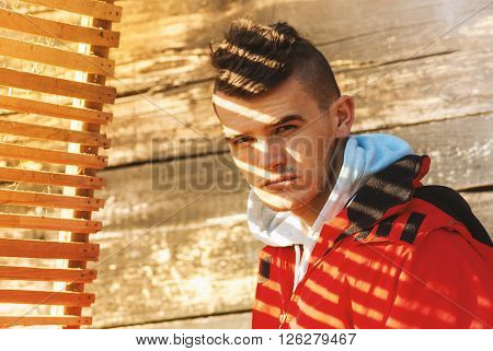 Young Man Posing In Red Jacket Covered With Beautiful Film Noir Style Shadow