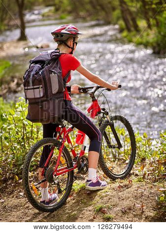 Bikes cycling girl with big rucksack cycling fording throught water .