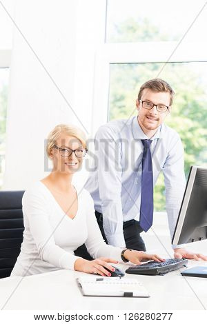 Office workers in formalwear working in office using computers. Business concept.