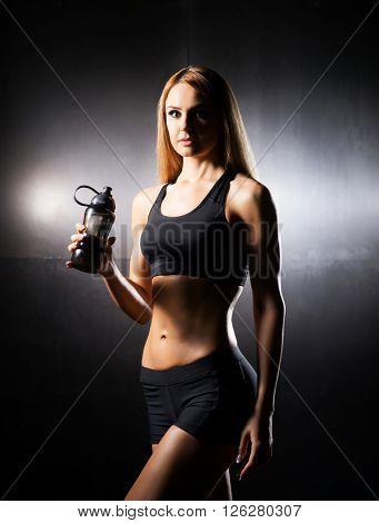 Fit, healthy and sporty woman in sportswear. Sporty girl drinks water.