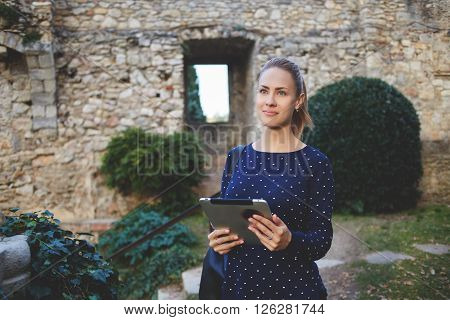 Young pretty female with digital tablet in hands is looking for someone while is standing at university campus. Woman tourist is using touch pad for navigation during her walking tour in old city