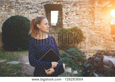 Thoughtful female student is holding digital tablet with empty screen while is standing at university campus. Charming college girl with touch pad in hands is resting after lectures in academy