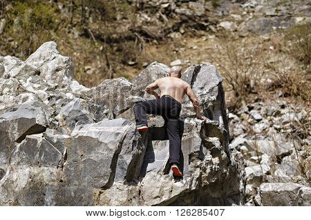 Man free climbing on huge boulders on a mountain