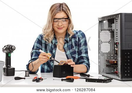 Female PC technician soldering a chip from a desktop computer isolated on white background