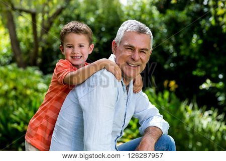 Side view of smiling garndfather with grandson at yard
